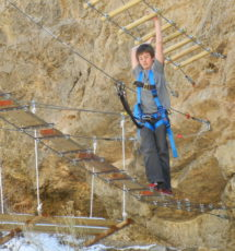 Teen boy making his way across the rope bridge Raft Masters Colorado