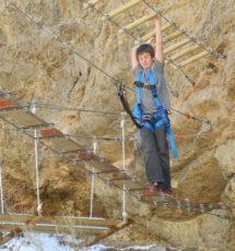 Teen boy making his way across the rope bridge Raft Masters Colorado