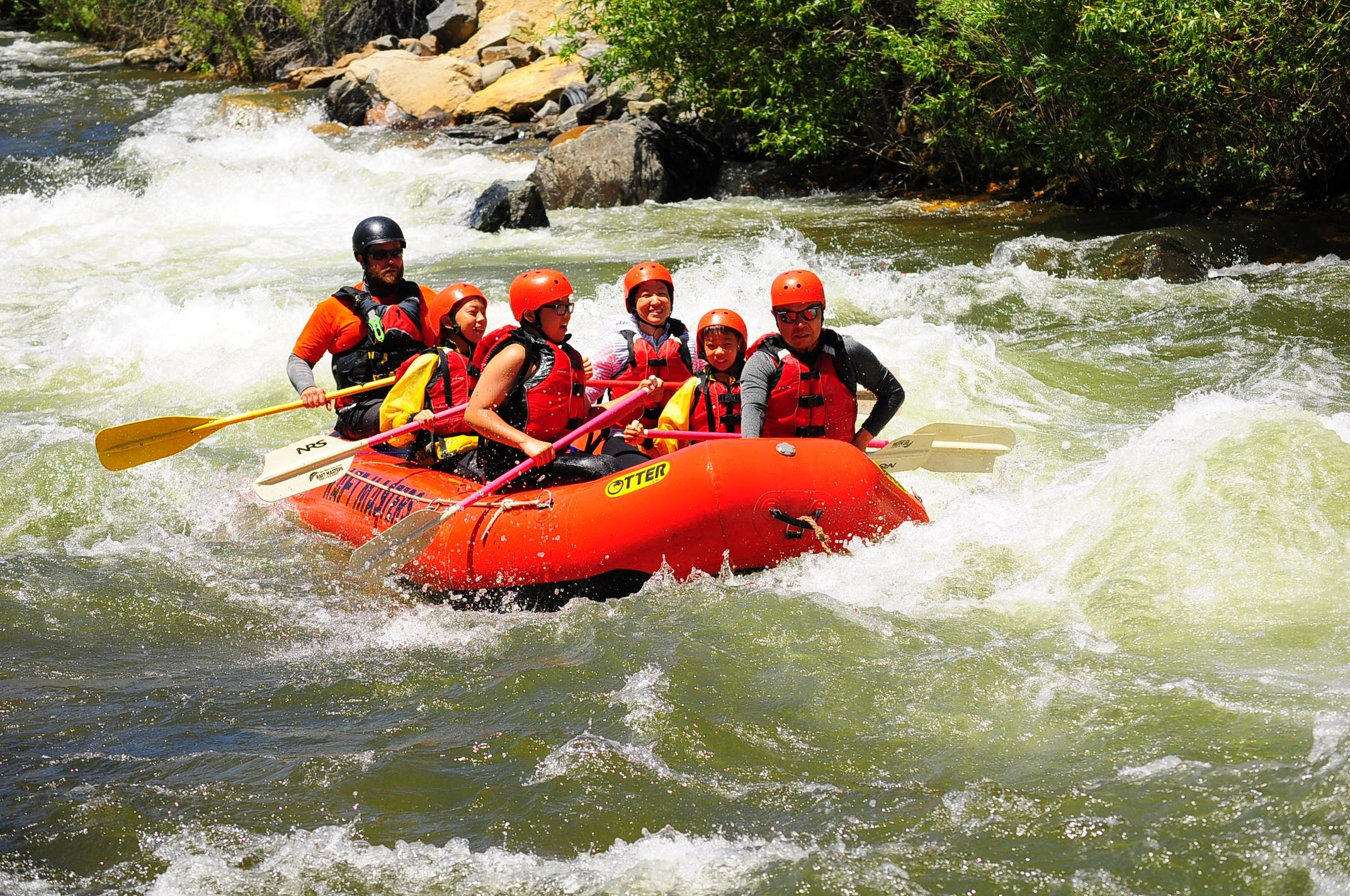 Raft with 5 guests and a guide going through rapids on Clear Creek Raft Masters Tours Colorado