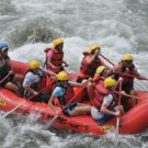 Group of guests in a raft going through rapids Raft Masters Tours Colorado
