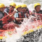 Close up of 5 guests in a raft with water splashing up Raft Masters Tours Colorado