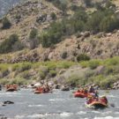 guests on raft navigating rapids with mountains in background on the Arkansas river Raft Masters Tours Colorado