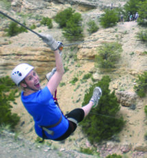 woman in blue shirt smiling while zip-lining Raft Masters Tours Colorado