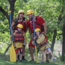 Two adults and two children posing with paddles and helmets on the riverbank Raft Masters Colorado