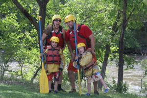 Two adults and two kids posing with paddles and helmets on the riverbank