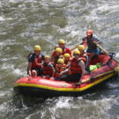 A family having fun in a raft going down the river Raft Masters