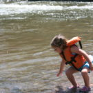 young girl with life jacket on the bank of the river Raft Masters Colorado