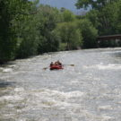 Family in a raft in the river going toward a bridge Raft Masters Colorado