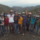 Group of people with helmets on and mountains in the background Raft Masters Tours Colorado