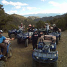 Group of people waving with ATVs and mountains in the background Raft Masters Tours Colorado