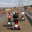 family of five riding segways across the bridge Raft Masters Colorado
