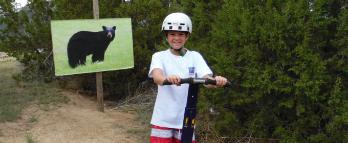 young boy on segway in front of bear sign Raft Masters Colorado