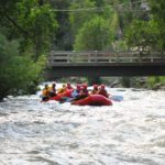 guests in rafts going down Clear Creek with a bridge in background Raft Masters Tours Colorado