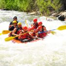 guests in raft smiling and going through rapids on Clear Creek Raft Masters Tours Colorado