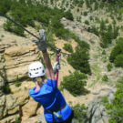 woman in blue shirt zip-lining Raft Masters Tours Colorado
