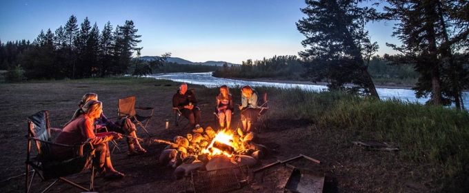 campfire at dusk next to river