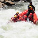 guests in raft dipping into the rapids on Clear Creek Raft Masters Tours Colorado
