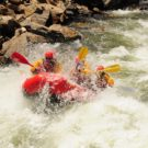guests in raft getting sprayed by water from rapids Raft Masters Tours Colorado